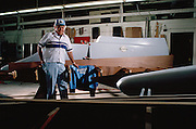 Ed Karelsen with a tunnel boat in the background and an inboard hydro in the foreground, shot at his shop for an article in Power Boat magazine. Ed won national and world championships in every division of power boat racing, but offshore. Most believe that the only reason he never won a championship there is because he never build a boat for offshore racing.