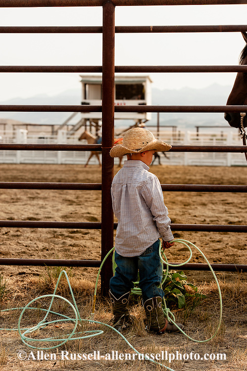 Wilsall Ranch Rodeo, boy admiringly watches cowboys, Wilsall, Montana