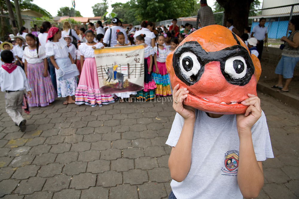 School children dressed as mascaradas on Guanacaste Day - 25th July. Santa Cruz, Guanacaste, Costa Rica.<br />