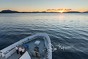 Three crew members on the National Geographic Explorer take a photo of sunrise in Aysen Fjord, Chile.