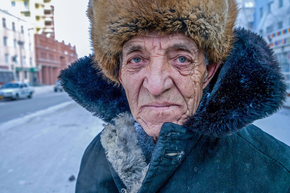 Street portrait of a Yakutsk inhabitant protected with the traditional fur cap and warm clothing against the extrem cold. Jakutsk is a city in the Russian Far East, located about 4 degrees (450 km) below the Arctic Circle. It is the capital of the Sakha (Yakutia) Republic (formerly the Jakut Autonomous Soviet Socialist Republic), Russia and a major port on the Lena River. Yakutsk is one of the coldest cities on earth, with winter temperatures averaging -40.9 degrees Celsius.
