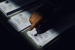 May 26, 2019 - Barcelona, Catalonia, Spain - A voters selects his ballots for the municipal elections in a polling station in Barcelona, during the European and municipal elections 2019. (Credit Image: © Matthias OesterleZUMA Wire)