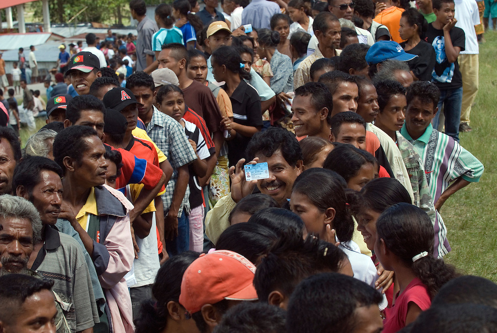 A man holds up his voter registration card as he stands in line to vote. Large number of East Timorese turn out in Ossu to cast their vote for either Francisco Guterres (Lu Olo) or Jose Ramos Horta, both candidates for East Timor's Presidential Elections.