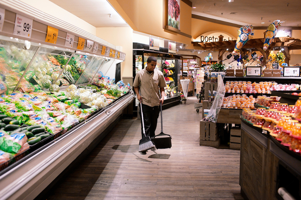 Elio Perdomo, sweeps the floor in the produce section at a Safeway grocery store in Silver Sping, MD. Perdomo, a student at Montgomery College, tries to take classes in the morning and works up to 16 hours a week at the supermarket.