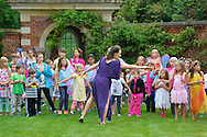Old Westbury, New York, USA. 28th June 2015. LORI BELILOVE, at center in purple tunic, of Lori Belilove & The Isadora Duncan Dance Company, gives dancing lessons to children throughout the gardens, and then perform on the South Lawn in front of the Mansion of historic Old Westbury Gardens, a Long Island Gold Coast estate, for its Midsummer Night event.
