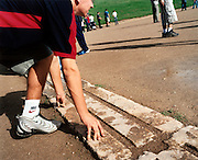 Nike trainers on the ancient Olympia's start line. A tourist crouches on the original marble starting line at ancient Olympia's athletics track where both ancient Greeks and Romans held their games. Nike was the Goddess of Victory to whom Olympic athletes made offerings and prayers before competition. Hercules is said to have paced out the 600 Greek feet, or 'Stadion,' from which we get the word 'Stadium'. Olympic spectators suffered dehydration due to to extreme heat. The 29th modern Olympic circus came home to Greece in 2004 and the birthplace of athletics was among the woodland of Ancient Olympia where for 1,100 continuous years, the ancients held their pagan festival of sport and debauchery. The modern games share many characteristics with its ancient counterpart. Corruption, politics and cheating interfered then as it does now and the 2004 Athens Olympiad will echo both what was great and horrid about the past.
