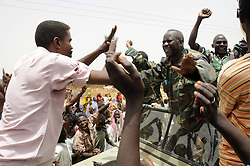 59722706.Soldiers wave to residents after returning from battlefield, in El Rahad of Sudan's North Kordofan State May 28, 2013. Sudanese army announced on Monday that it has liberated the strategic area of Abu Karshula in South Kordofan State from rebels of the Revolutionary Front. May 28, 2013..UK ONLY
