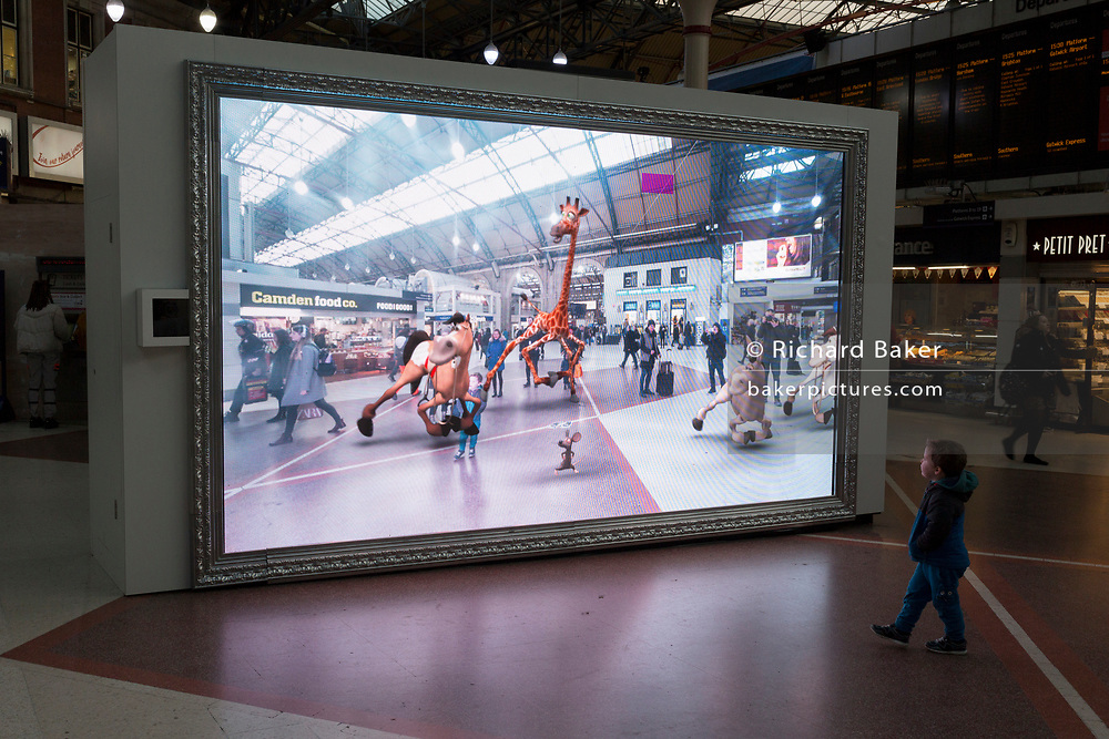 As young child is captivated by a large screen showing an augmented reality world of the station concourse and fantasy creatures, part of a loop of ads for Visit Scotland and for HBO's Game of Thrones, in London, England, on 4th December 2019.