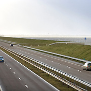 Nederland Den Oever Zurich 22 november 2008 20081122 Foto: David Rozing ..Serie afsluitdijk. De Afsluitdijk is een belangrijke waterkering en verkeersweg in Nederland. De waterkering sluit het IJsselmeer af van de Waddenzee. Hieraan ontleent de dijk zijn naam. De verkeersweg, onderdeel van Rijksweg a7, verbindt Noord-Holland met Friesland...Snelweg afsluitdijk, rechts standbeeld van Cornelis Lely, gemaakt door beeldhouwer Mari Andriessen. Cornelis Lely was in 1913 minister van waterstaat en stond aan de wieg van de afsluitdijk.  weg, wegen, autoweg, rijstroken, auto, auto's, deltaplan..Foto David Rozing