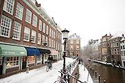 Een fietser rijdt door de sneeuw in Utrecht. In grote delen van Nederland is vandaag voor het eerst sneeuw gevallen