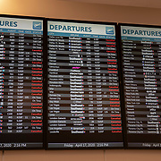 The information board at Orlando International Airport shows the cancellations of departing flights on Friday, April 17, 2020 in Orlando, Florida. (Alex Menendez via AP)