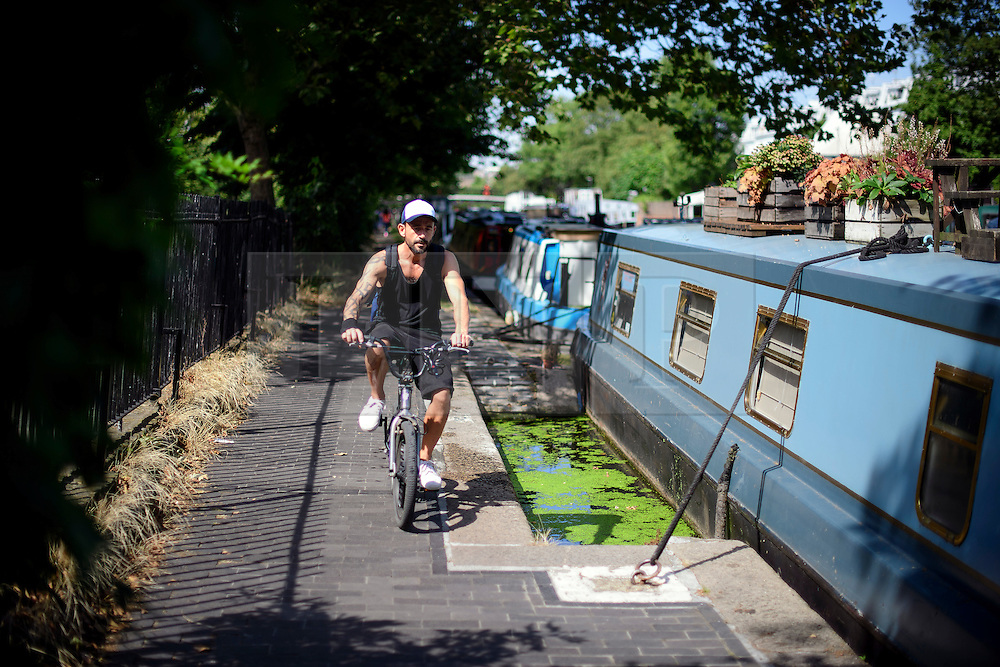 © Licensed to London News Pictures. 24/08/2016. London, UK. A man rides his bike in the sunshine along the Grand Union Canal in Little Venice, West London as warm weather across the UK continues.. Photo credit: Ben Cawthra/LNP