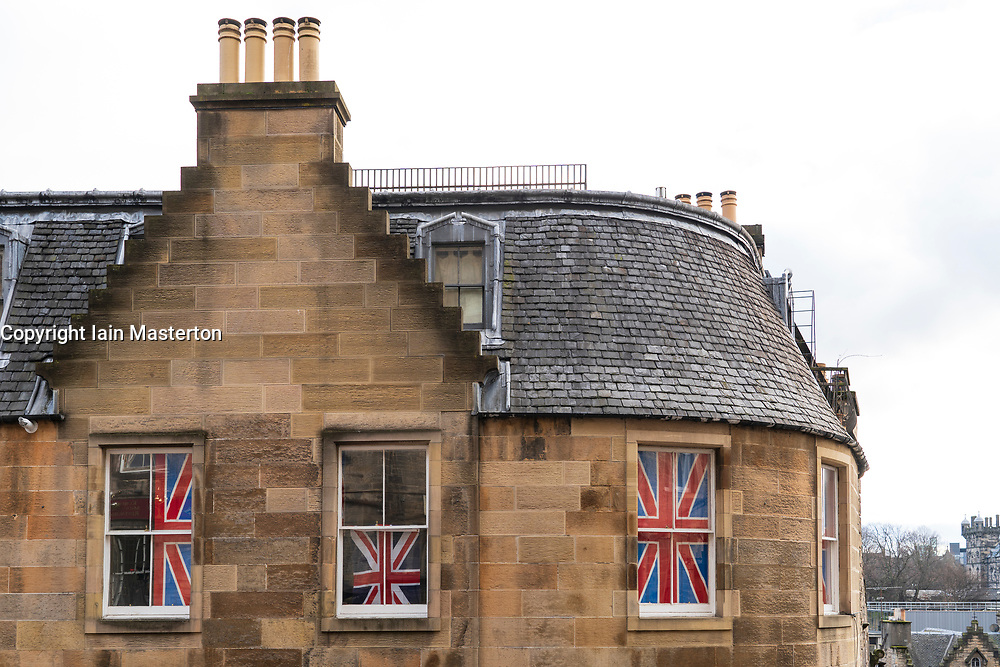 Old apartment building with Union Jack flags in the windows in Edinburgh Old Town , Scotland, UK