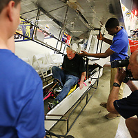 Wayne Carini, of the television show Chasing Classic Cars, is helped into the Houston Solar Race Team's solar car by Derrion Pulphus, a tenth grader at Houston High School and his teammates, as Carini learned about the build and function of car during their time together at the Bonhams Preview Day at the Tupelo Automobile Museum Thursday. The students were filmed for a future Chasing Classic Cars episode.