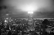 On Jan 13 looking from Madison Ave in Midtown.The brightly lit tip of the Empire State building dissappears inot the clouds. New York. 1992. © Copyright Photograph by Dafydd Jones 66 Stockwell Park Rd. London SW9 0DA Tel 020 7733 0108 www.dafjones.com