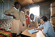 Nairobi, June 2010 - Volunteer Franny Noble records the names  of girls at the Agape hope center as they prepare to be in a group photo. the