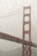 Looking at the Golden Gate Bridge through a window covered in raindrops.