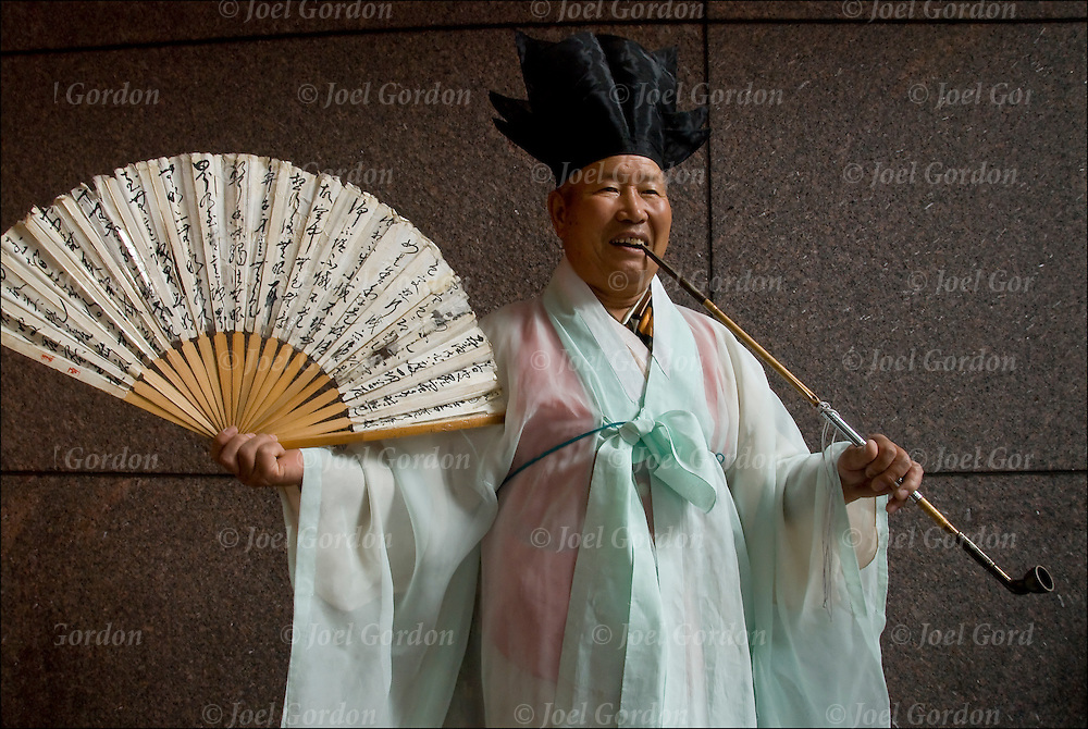 Annual Korean Harvest Parade in New York City. Portrait of  Korean-American elderly man  with opium pipe smiling wearing traditional Korean folk costume.