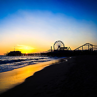 Photo of Santa Monica Pier sunset over the Pacific Ocean in California. Santa Monica Pier is a landmark that has an amusement park with a ferris wheel, roller coaster, restaurants, and other attractions.