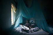 A boy is safely tucked in under a mosquito net. Mosquito nets save lives.