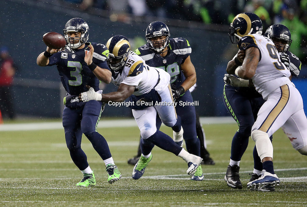 Seattle Seahawks quarterback Russell Wilson (3) throws a forward pass good for a gain of 9 yards to the St. Louis Rams 26 yard line while being chased by St. Louis Rams defensive end William Hayes (95) during the 2015 NFL week 16 regular season football game against the St. Louis Rams on Sunday, Dec. 27, 2015 in Seattle. The Rams won the game 23-17. (©Paul Anthony Spinelli)
