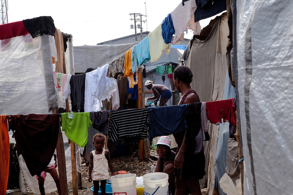 Daily life in the makeshift refugee camp, La Piste, in Port-au-Prince, Haiti on July 17, 2010. La Piste (French for &quot;runway&quot;)is a settlement sprawled across the site of a disused airport and now home to an estimated 20,000 earthquake survivors living in makeshift structures.<br /> Six month after a catastrophic earthquake measuring 7.3 on the Richter scale hit Haiti on January 13, 2010, killing an estimated 230,000 people, injuring an estimated 300,000 and making homeless an estimated 1,000,000.