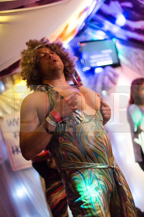 © Licensed to London News Pictures. 27/06/2015. Pilton, UK.  Night-time festival atmosphere at Glastonbury Festival 2015 in the Shangri-La area of the festival - a male performer caresses his fake breasts on stage at the Kamikaze Karaoke bar.  On Saturday Day 4 of the festival.  Shangri-La is a destroyed dystopian pleasure city.  This years headline acts include Kanye West, The Who and Florence and the Machine, the latter being upgraded in the bill to replace original headline act Foo Fighters. Photo credit: Richard Isaac/LNP