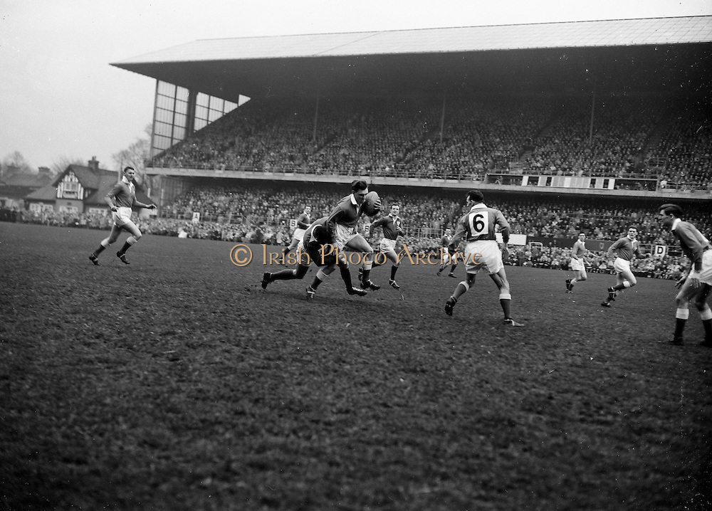 Welsh captain and left centre back B J Jones is well tackled by Irish forward N A A Murphy, with Dave Hewitt on the right, following up, ..Irish Rugby Football Union, Ireland v Wales, Five Nations, Landsdowne Road, Dublin, Ireland, Saturday 12th March, 1960,.12.3.1960, 3.12.1960,..Referee- D A Brown, Rugby Football Union, ..Score- Ireland 9 - 10 Wales, ..Irish Team, ..T J Kiernan,  Wearing number 15 Irish jersey, Full Back, University college Cork Football Club, Cork, Ireland,  ..W W Bornemann, Wearing number 14 Irish jersey, Right Wing, Wanderers Rugby Football Club, Dublin, Ireland, ..D Hewitt, Wearing number 13 Irish jersey, Right centre, Queens University Rugby Football Club, Belfast, Northern Ireland,..A C Pedlow, Wearing number 12 Irish jersey, Left Centre,  C I Y M S Rugby Football Club, Belfast, Northern Ireland, ..D C Glass, Wearing number 11 Irish jersey, Left Wing, Collegians Rugby Football Club, Belfast, Northern Ireland,..S Kelly, Wearing number 10 Irish jersey, Outside Half, Landsdowne Rugby Football Club, Dublin, Ireland, ..A A Mulligan, Wearing number 9 Irish jersey, Captain of the Irish team, Scrum Half, London Irish Rugby Football Club, Surrey, England, ..S Millar, Wearing number 1 Irish jersey, Forward, Ballymena Rugby Football Club, Antrim, Northern Ireland,..B McCallan, Wearing number 2 Irish jersey, Forward, Ballymena Rugby Football Club, Antrim, Northern Ireland,..B G Wood, Wearing number 3 Irish jersey, Forward, Landsdowne Rugby Football Club, Dublin, Ireland,..W A Mulcahy, Wearing number 4 Irish jersey, Forward, University College Dublin Rugby Football Club, Dublin, Ireland, ..M G Culliton, Wearing number 5 Irish jersey, Forward, Wanderers Rugby Football Club, Dublin, Ireland, ..N Murphy, Wearing number 6 Irish jersey, Forward, Cork Constitution Rugby Football Club, Cork, Ireland,..T McGrath, Wearing number 7 Irish jersey, Forward, Garryowen Rugby Football Club, Limerick, Ireland, ..J R Kavanagh, Wearing number 8 Irish jersey, Forward, Wande