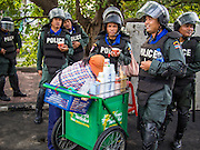 14 DECEMBER 2013 - BANGKOK, THAILAND:  Thai riot police on duty near Government House snack on ice cream. The Thai anti-government movement, called the People's Democratic Reform Committee (PRDC) sponsored a forum Saturday to establish guidelines for political reform in Thailand. The opposition leader, Suther Thaugsuban, said his movement will not participate in a similar forum, sponsored by the government scheduled for Sunday. Thailand's political impasse continues with the opposition calling for the caretaker government of Prime Minister Yingluck Shinawatra to step down. Yingluck has, so far, refused to step down from her caretaker roll. Crowds at the anti-government rallies have shrunk substantially since the collapse of the government earlier in the week.       PHOTO BY JACK KURTZ
