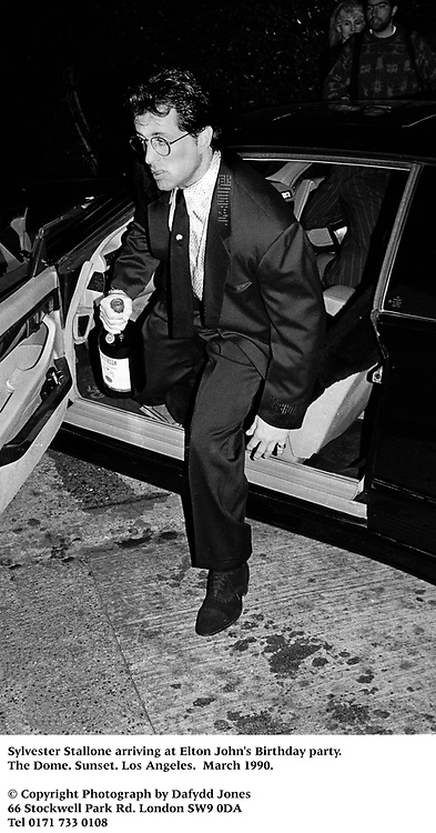 Sylvester Stallone arriving at Elton John's Birthday party. the Dome. Sunset. Los Angeles.  March 1990.<br />