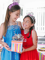 Portrait of two girls (7-9 10-12) in tiaras holding present smiling