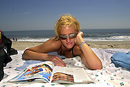 Jeana Coutts, 22, of Doylestown, Pa., reads a magazine as she relaxes on the beach at the start of the Memorial Day weekend, Friday, May 24, 2002, in Cape May, N.J. (Photo by William Thomas Cain/photodx.com)