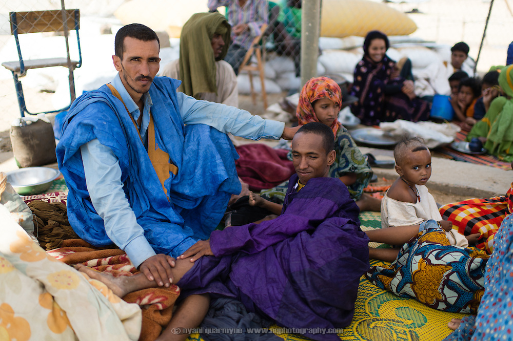 Mohamed Ag Taher (left) and his family waiting outside the fence of a transit camp in Fassala in southeastern Mauritania on 4 March 2013 before being registered as refugees. After spending the night in Fassala, they will be driven in a convoy to the main refugee camp of Mbera.