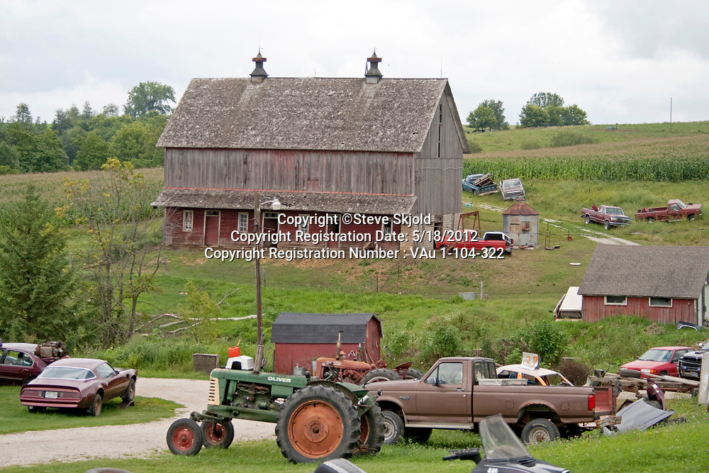 Old barn surrounded by cars tractors and field of corn Lanesboro Minnesota MN USA