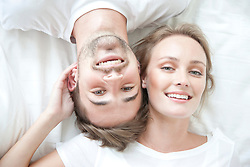 Smiling Couple Lying on Bed Facing Opposite Directions