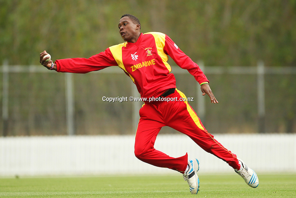 Tafadzwa Kamungozi of Zimbabwe takes a diving catch to dismiss Corey Anderson of the Black Caps during the ICC Cricket World Cup warm up game between the Black Caps v Zimbabwe at Bert Sutcjliffe Oval, Lincoln, Christchurch. 9 February 2015 Photo: Joseph Johnson / www.photosport.co.nz