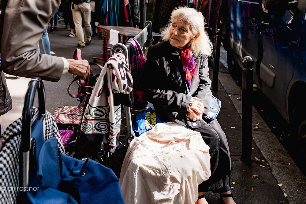 Woman selling cloths in a street garage sale in Paris