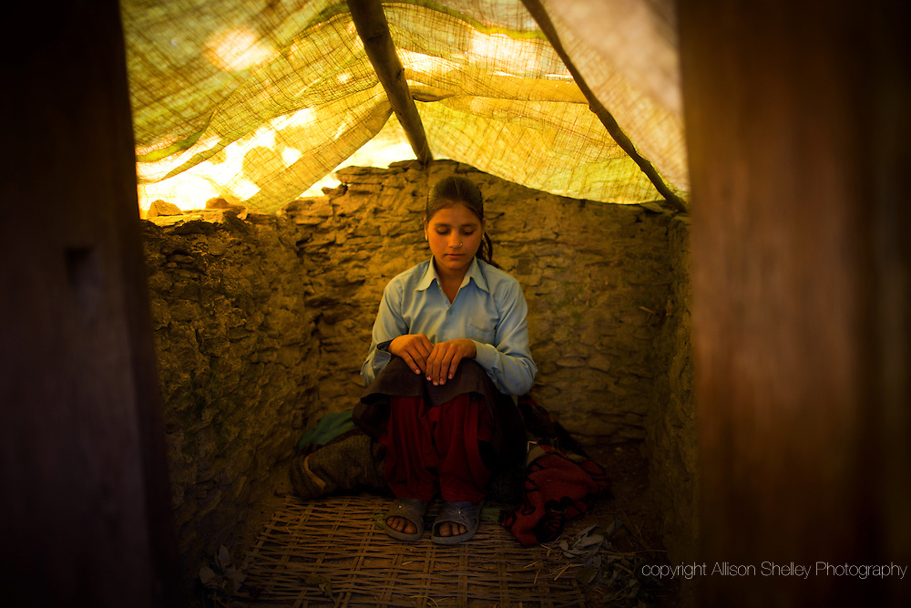 Still in her school uniform, Jaukala, 14, poses for a photo in the family's chaupadi shelter, a squat shed measuring approximately one meter by two meters, apart from the home where the women of the household sleep during their periods, in Rima village, Achham, Nepal. A tarp serves as a temporary roof to this structure, still under construction.