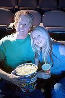 Young Couple sitting close lying on shoulder Watching Movie Together in theatre