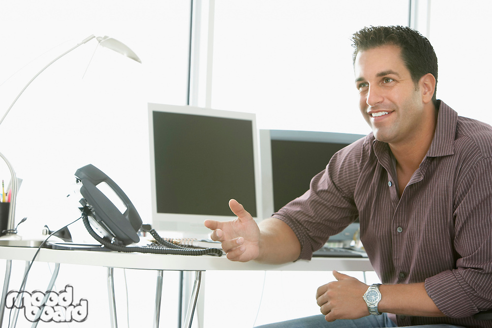 Businessman smiling by computers in office