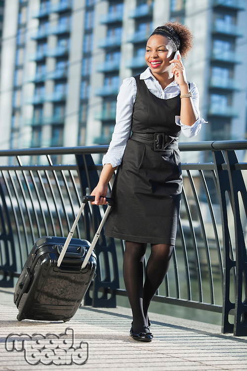 African American businesswoman in formal clothing walking with wheeled bag while on call