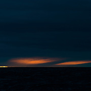 As the sun dips below the horizon for a brief summer night it casts a glow on the clouds above, broken by a shadow from a large iceberg over the horizon.