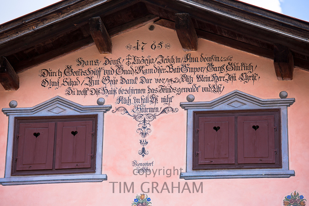 Window shutters, inscription and paint effects on 18th Century house built 1765 in Klosters, Graubunden, Switzerland