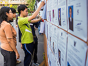 30 MARCH 2014 - BANGKOK, THAILAND:   Voters check to see if their names are on the voting rolls at the polling place at Wat That Thong in Bangkok. Thais voted Sunday to elect 77 senators to the 150-seat Senate. The other 73 senators are appointed by judges and senior officials from agencies such as the National Anti-Corruption Commission (NACC), members of an establishment whom government supporters see as viscerally anti-Thaksin. The government of Yingluck Shinawatra tried to make the senate a fully elected body. That effort was one of the sparks that set off the latest rounds unrest that started in November.   PHOTO BY JACK KURTZ