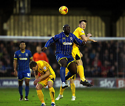 Adebayo Akinfenwa of AFC Wimbledon is challenged in the air by Ollie Clarke of Bristol Rovers - Mandatory byline: Robbie Stephenson/JMP - 07966 386802 - 26/12/2015 - FOOTBALL - Kingsmeadow Stadium - Wimbledon, England - AFC Wimbledon v Bristol Rovers - Sky Bet League Two