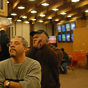 Friends Carlos Hosking, from left, Freddy Cocco and Eduardo Polanco react to the conclusion of a Simulcast Santa Anita race after the end of the live racing at the Aqueduct racetrack in New York City on February 19, 2007. Hosking, who says he loses about a third of his salary from his public school custodial job as at the race track every year, lost $96, Cocco won his bet and Polanco lost $20...Betting on the horses is still a popular game and the money still flows, but off track betting and other forms of entertainment have eroded live attendance at the races.  The daily diehard betters and horse lovers who sparsely populate the place on work days are joined by a bigger crowd on the weekends. ..The Aqueduct, located in Ozone Park, Queens, is the only horse racing track in New York City and probably the coldest in the country (most of the others are in Kentucky, Florida or California). Horses race on the winterized inner dirt rack from January 1st through the end of April. Aqueduct was built in 1894, renovated in 1959, then opened for winter racing in 1975. It is the winter race track operated by the New York Racing Association (NYRA), which also runs Belmont and Saratoga in the warm seasons. Betters at Aqueduct watch and bet on the nine daily live races and all other races around the country via Simulcast. ..