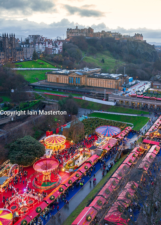Overhead view of Edinburgh Christmas market in Princes Street Gardens at dusk with Edinburgh Castle in the background, Edinburgh, Scotland, UK