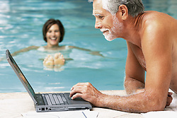 Dec. 05, 2012 - Man and woman in swimming pool with computer (Credit Image: © Image Source/ZUMAPRESS.com)