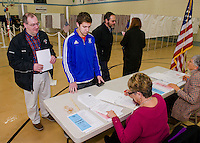 "Peter Karagianis looks on as his son Christian checks in as a ""first time"" voter with Donna Mooney at the Gilford Community Center during the NH Primary on Tuesday morning.  (Karen Bobotas/for the Laconia Daily Sun)"