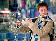 A young street musician playing the flute in a street in Tel Aviv, Israel